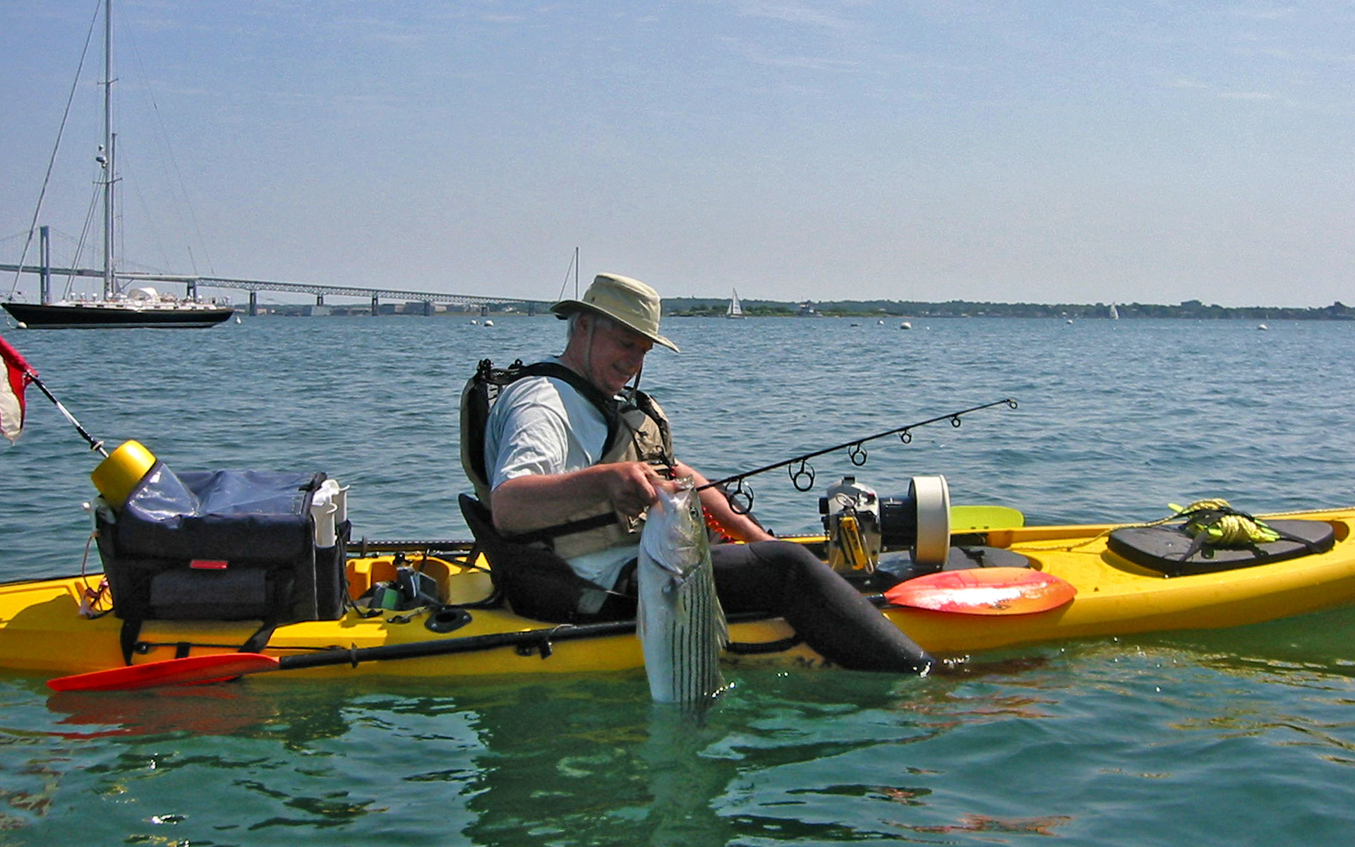 Mike Laptew removing the hook from a striped bass next to his Ocean Kayak