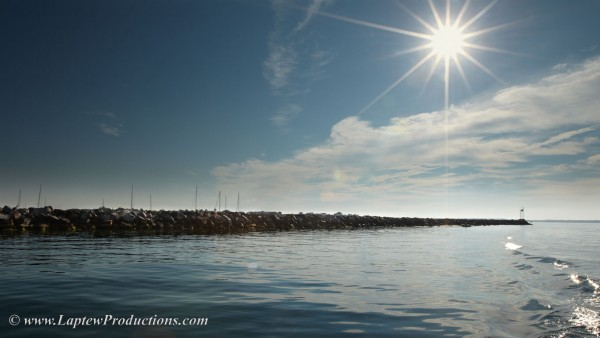 sun shines down on breakwater in Little Narragansett Bay